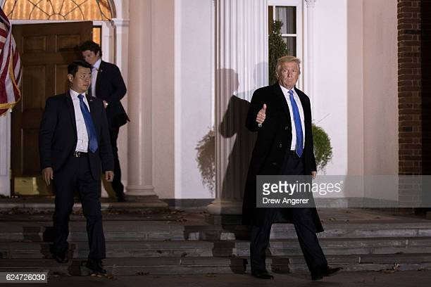 Trailed by US Secret Service agents Presidentelect Donald Trump leaves the clubhouse following a full day of meetings at Trump International Golf...