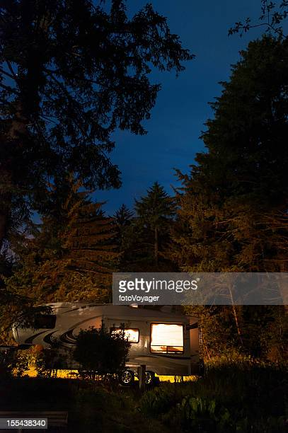 Trailer illuminated in state park under starry skies USA