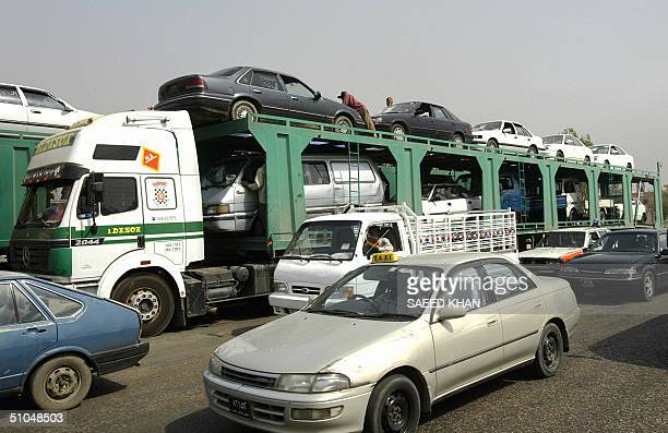 A trailer loaded with secondhand cars imported from Jordan arrives at one of the automobile market on the outskirts of Baghdad 11 July 2004 Thousands...