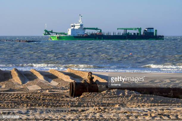 DEME trailing suction hopper dredger Uilenspiegel at sea used for sand replenishment / beach nourishment to make wider beaches to reduce storm damage
