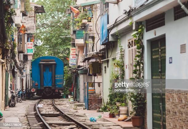 train amidst buildings in city - bortes photos et images de collection