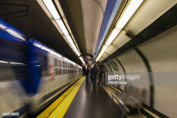 Train and people moving through a Metro station
