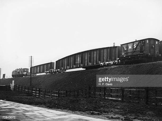 A train arrives carrying the two 50ton main girders of a new bridge to be built over Thorpes Road on the LMS line between Hanbury Staffordshire and...