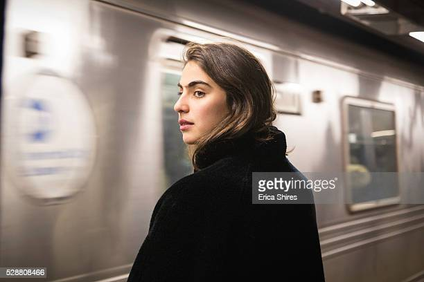 train arriving at station while woman waits - new york city subway stock pictures, royalty-free photos & images