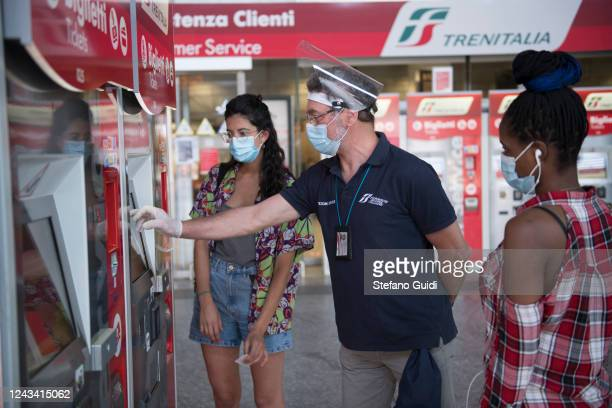 A train attendant wear a protective mask and gloves helps two travellers to buy train tickets from an automatic ticket machine at the Porta Nuova...