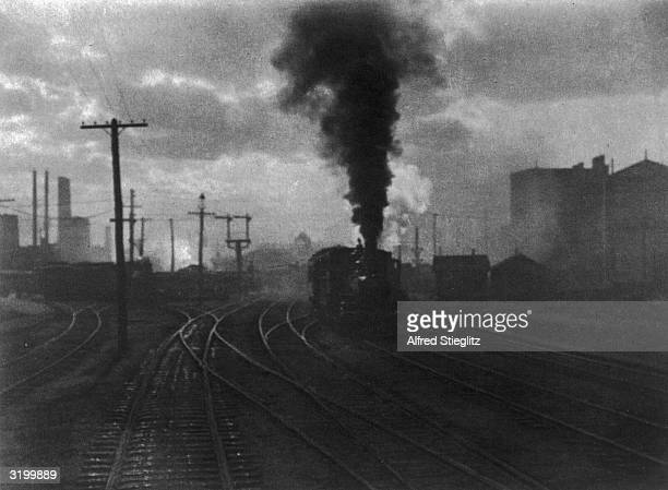 A train blows black smoke and rumbles down the tracks as a city protrudes through a thick haze in the background