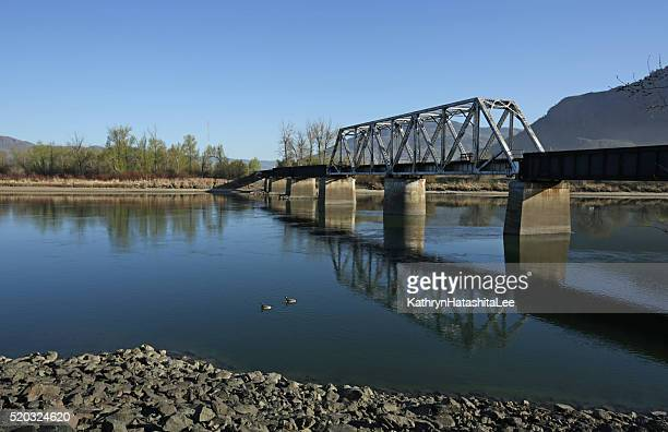 train bridge over south thompson river, kamloops, british columbia, canada - kamloops stock pictures, royalty-free photos & images