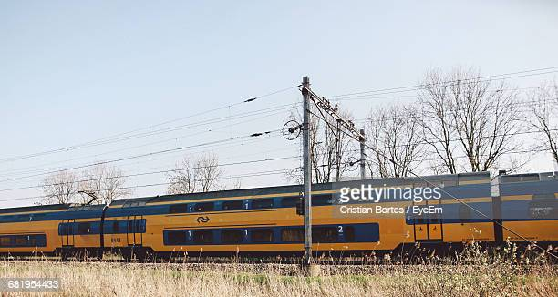 Train By Grassy Field Against Clear Sky