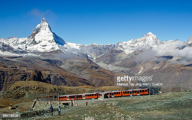 Train By Snow Covered Mountains Against Clear Blue Sky