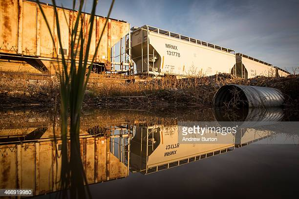 Train cars sit next to miles of unused pipe prepared for the proposed Keystone XL pipeline on October 14 2014 outside Gascoyne North Dakota