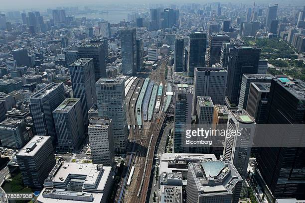 A train center bottom travels along a railway track while platforms at Tokyo Station center sit among commercial and residential buildings in this...