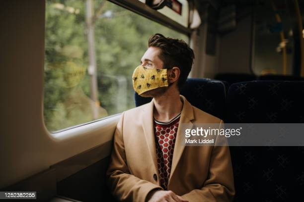 train commuter wearing ppe face mask for safety - travel stock pictures, royalty-free photos & images