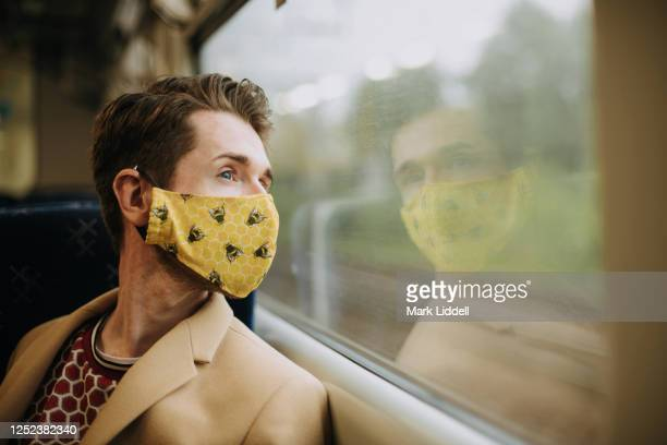 train commuter wearing ppe face mask for safety - obscured face stock pictures, royalty-free photos & images