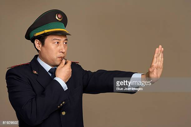 Train conductor blowing whistle and gesturing