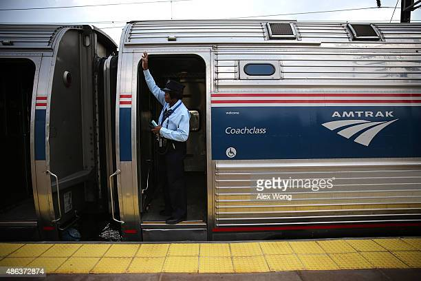A train conductor signals from an Amtrak train September 3 2015 in New Carrollton Maryland US Secretary of Homeland Security Jeh Johnson held a press...