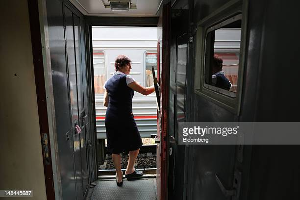 A train conductor stands in the open doorway of a rail carriage aboard the MurmankSochi train operated by OAO Russian Railways at Pridacha station in...