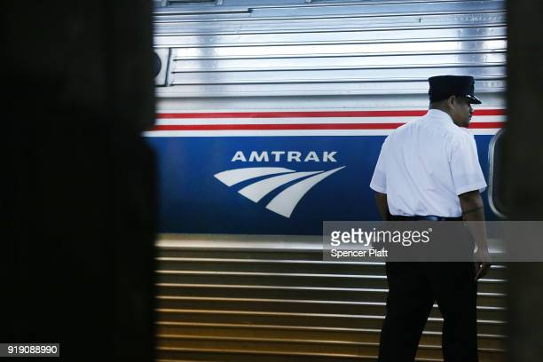A train conductor stands next to an Amtrak train at New York's Pennsylvania Station on February 16 2018 in New York City Amtrak gave a media tour on...