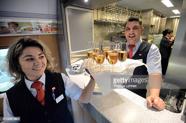A train conductor takes a tray with sparkling wine glasses at the board restaurant of the latest generation of the ICE 3 Deutsche Bahn highspeed...