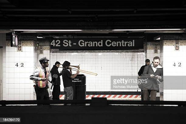 CONTENT] Train conductor trombone player and straphangers wait for a morning train at Grand Central Station New York City