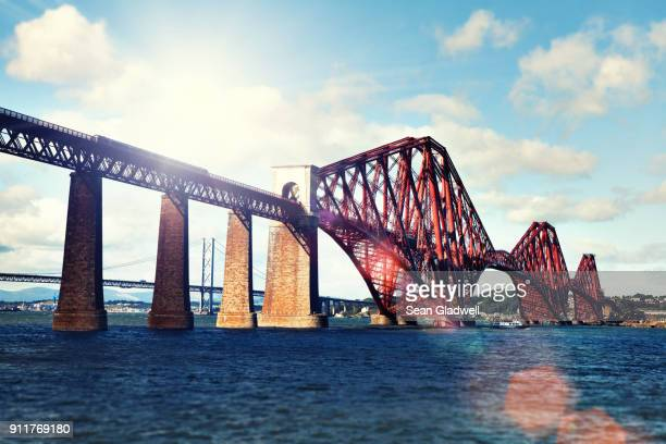 train crossing the forth bridge - international landmark stock pictures, royalty-free photos & images