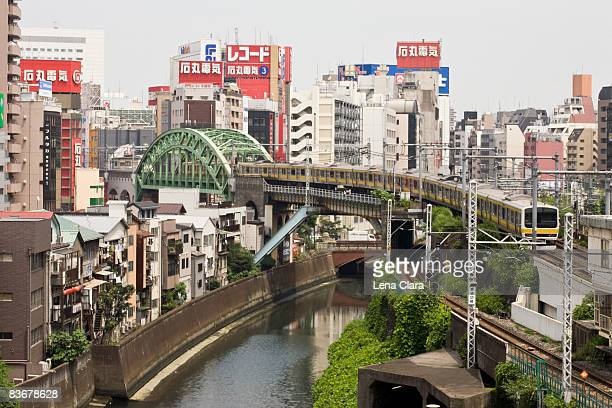 train crossing the kanda river with akihabara district in background, tokyo - akihabara stock pictures, royalty-free photos & images