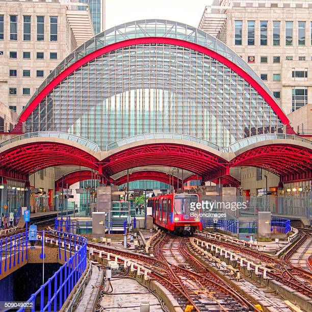 dlr train departs iconic canary wharf station on rainy day - urban renewal stock pictures, royalty-free photos & images