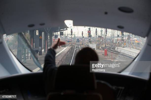 A train driver gestures in the cabin of a Siemens AG 407 series InterCity Express 3 VelaroD train operated by Deutsche Bahn AG at the central railway...
