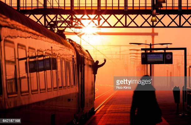 Train driver in locomotive waving as the train departs from station at sunset