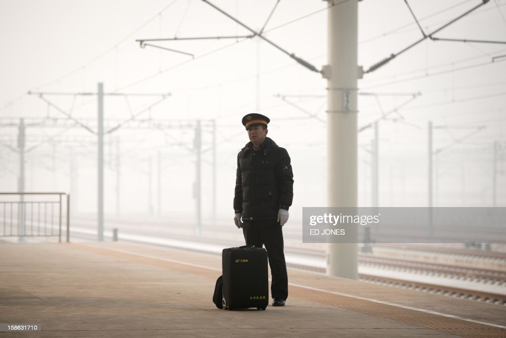 A train driver stands at a high-speed rail platform in Hebei province near Beijing on December 22, 2012. China showed off the final link of the world's longest high-speed rail route, set to open on December 26, stretching from Beijing to the southern Chinese city of Guangzhou. Travelling at around 300 kph, trains on the new route are expected to cover the 2,298-kilometre (1,425-mile) journey in a third of the current time from 22 hours to eight. AFP PHOTO / Ed Jones
