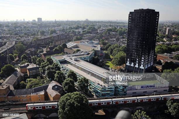 A train drives past Grenfall tower as it continues to smoulder on June 15 2017 in London England At least twelve people have been confirmed dead and...