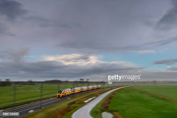 Train driving in a rural landscape during a dark day