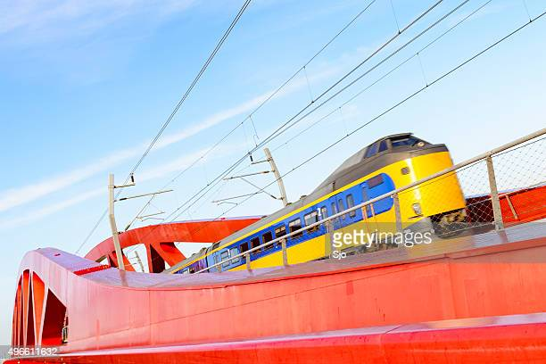 Train driving over a red modern design bridge
