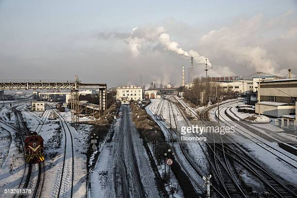 A train engine travels on tracks in the Erdaojiang district as water vapor and smoke rise from a Tonghua Iron Steel Group Co plant in the distance in...