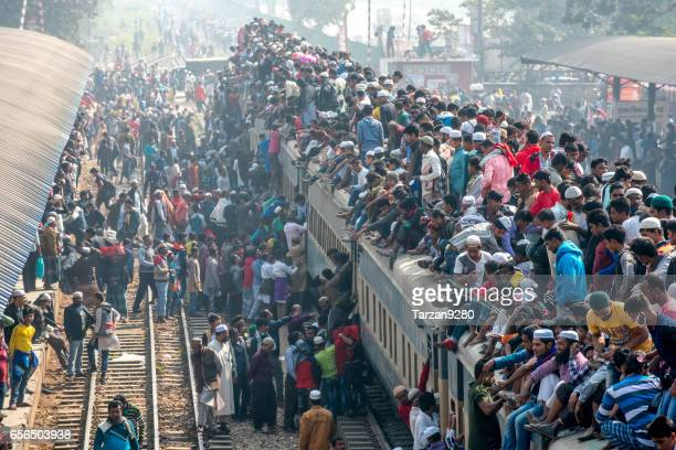 train full of passengers entering station on misty day - bangladesh stock pictures, royalty-free photos & images