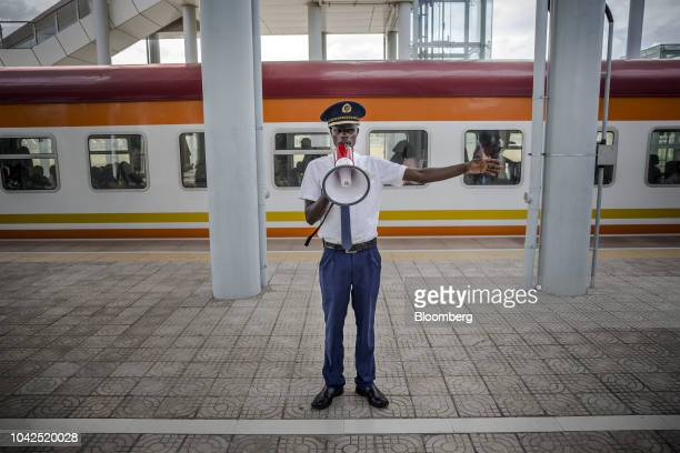 A train guard uses a megaphone to instruct rail travelers on a platform at Mombasa SGR Terminus station in Mombasa Kenya on Saturday Sept 1 2018...