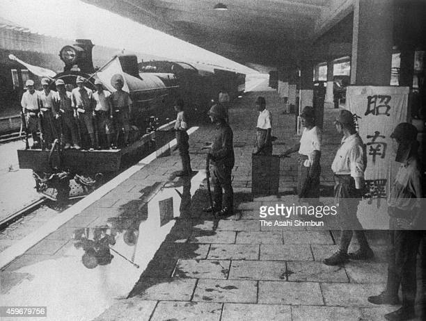 A train hoisting the Japanese national flags apporaches to a platform of 'Shonan' station after the fall of Singapore and renamed to Shonan circa...