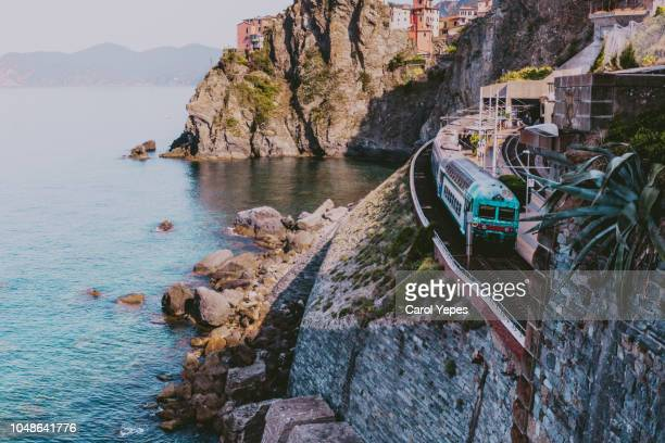train in coastline in manarola,cinque terre,italy - liguria stock photos and pictures