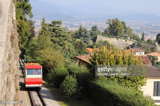 train in track by trees against mountains and sky - bergame photos et images de collection