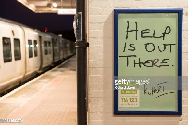 Train is stopped at Loughborough Junction railway station where a Samaritan's poster urges those with mental health issues, or even thoughts of...