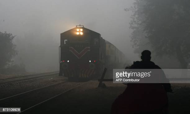 A train leaves a railway station amid heavy smog in Lahore on November 12 2017 Large swathes of Pakistan and north India see a spike in pollution at...