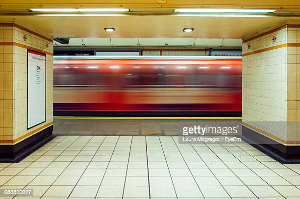 train leaving gants hill underground train station platform in london - red tube stock pictures, royalty-free photos & images
