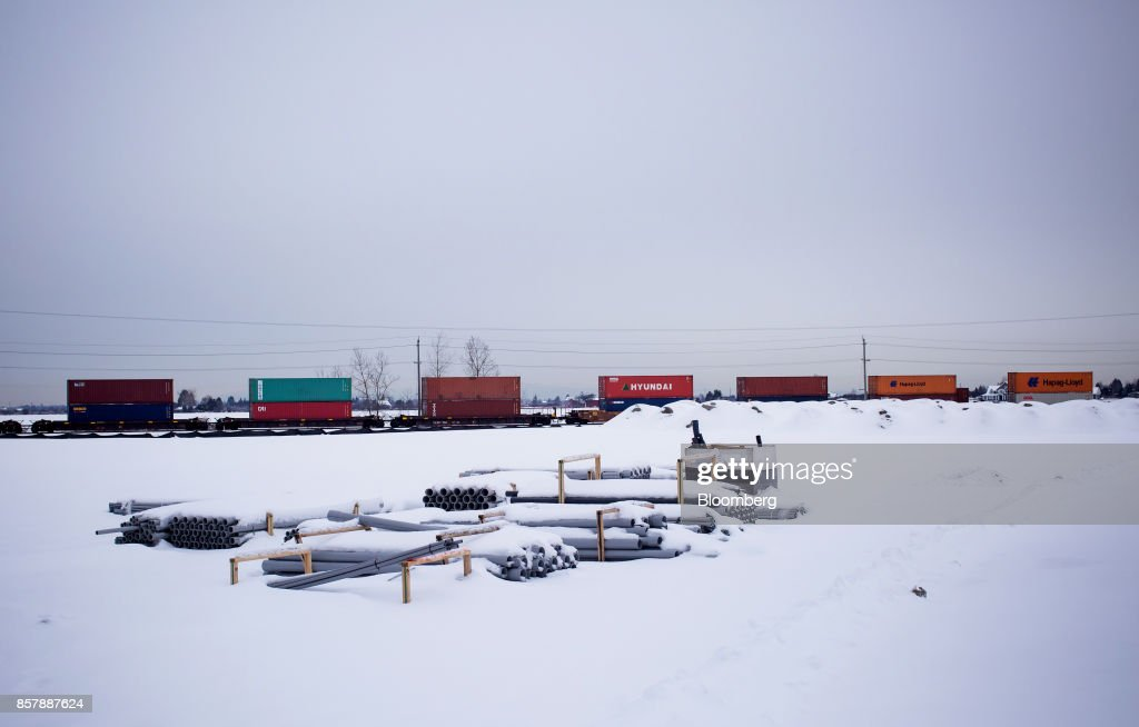 A train loaded with shipping containers moves past the Deltaport Logistics Facility construction site in Tsawwassen, British Columbia, Canada, on Wednesday, Feb. 8, 2017. The new Tsawwassen Mills mall is just one manifestation of the economic boom underway in Tsawwassen First Nation, an aboriginal community about 20 miles from both downtown Vancouver and the U.S. border. Nearby, there's a master-planned residential development where homes start at C$619,900. A little further down the road, the Tsawwassen are expanding a logistics center serving the country's busiest commercial port. Photographer: Ben Nelms/Bloomberg via Getty Images