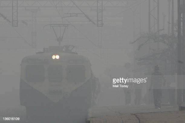 A train moves amidst dense fog during morning office hours in New Delhi on Monday A thick fog disrupted road and rail traffic at several places in...