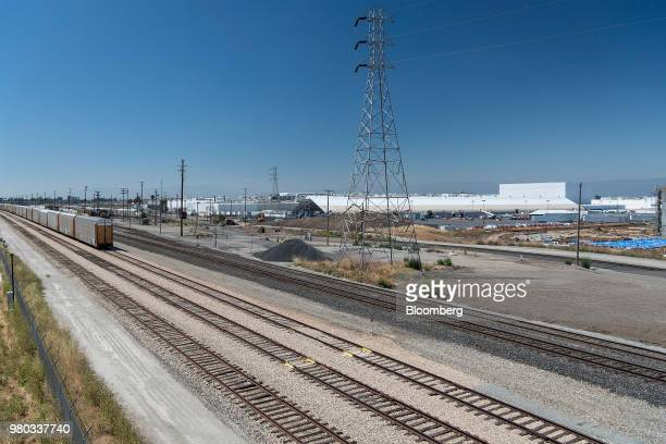 A train moves past a newly constructed production tent at the Tesla Inc manufacturing facility in Fremont California US on Wednesday June 20 2018...