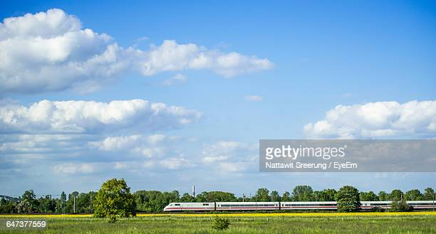 train moving by grassy landscape against sky - tyskland bildbanksfoton och bilder