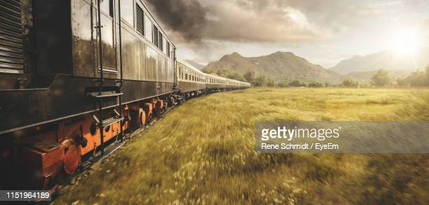 train moving on railroad track against cloudy sky - austria stock pictures, royalty-free photos & images