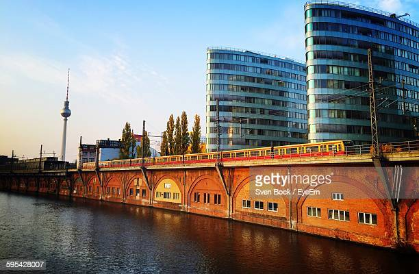 Train Moving On Railway Bridge By Fernsehturm And Buildings Against Sky