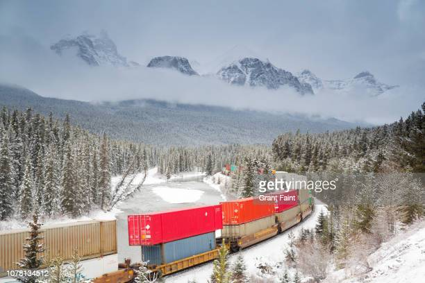 train moving through mountains. - canadian rockies stock pictures, royalty-free photos & images