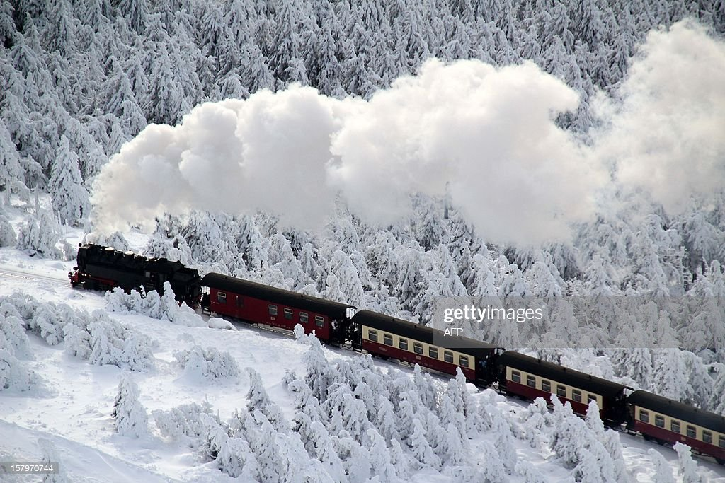 A train of the Brocken Railway steams through the winter landscape with snow covered pine trees on Brocken Mountain in Harz,eastern Germany, on December 8, 2012. AFP PHOTO / Stefan Rampfel /GERMANY OUT