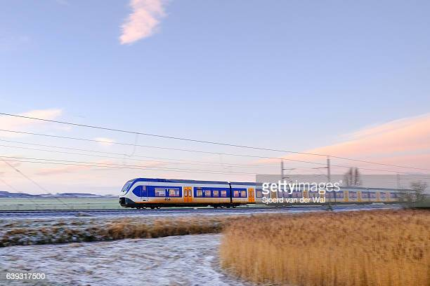 train of the dutch railways driving through frozen winter landscape - sjoerd van der wal or sjo stockfoto's en -beelden